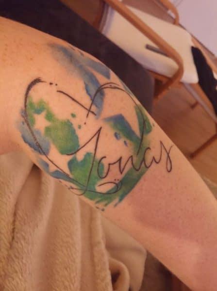 Tattoo am Oberarm mit Sternen und Name