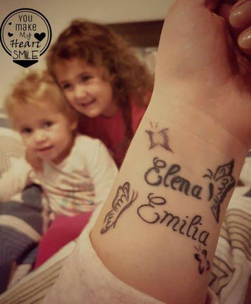 Gezeigt wird ein Tattoo am Handgelenk mit zwei Kindern (verschwommen) im Hintergrund